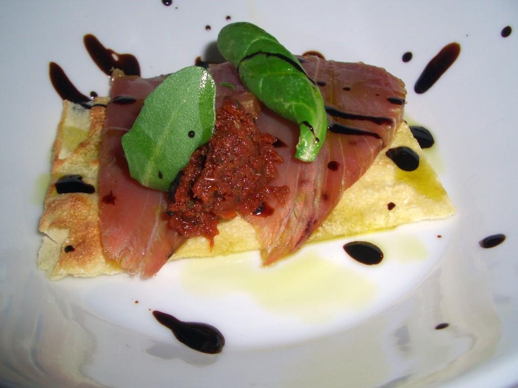 Atún rojo ahumado sobre regaña de pan cristal y picada de tomates secos y orégano