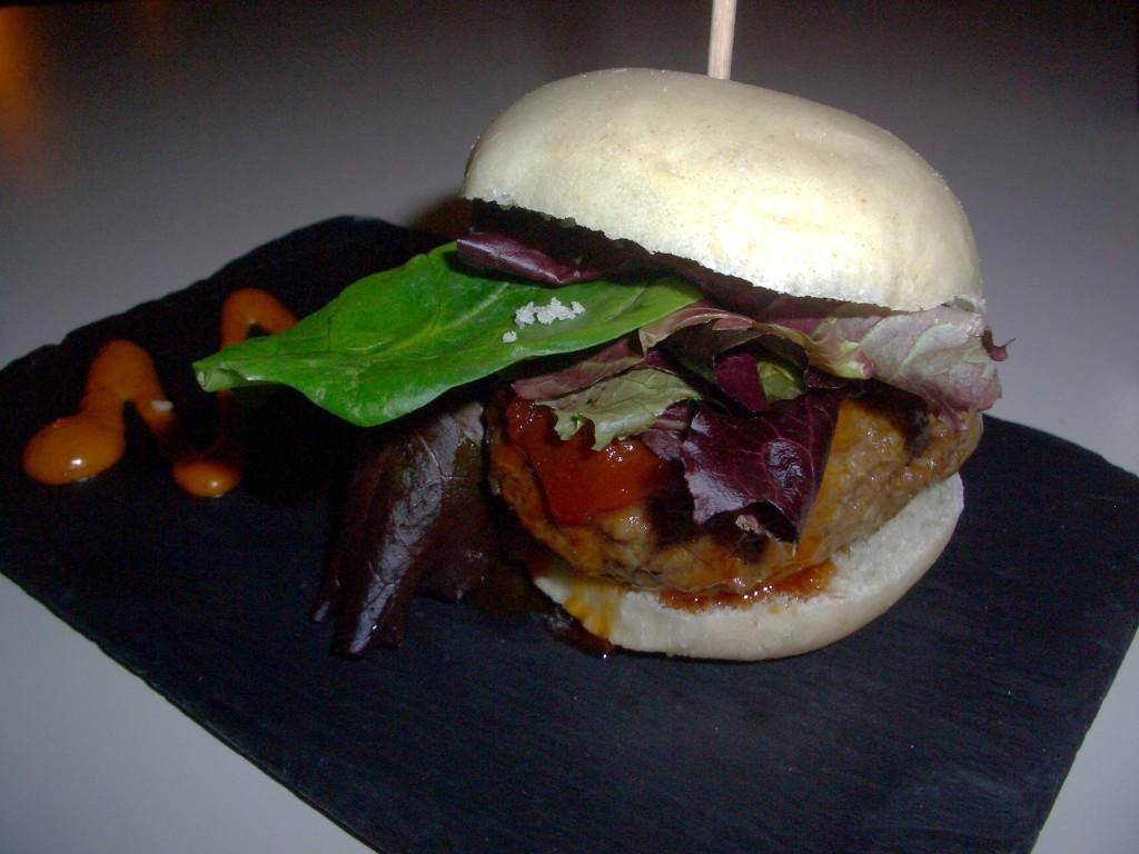 Mini hamburguesa de buey con confitura de tomate y brotes tiernos