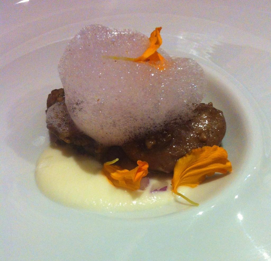 Castañetas de cerdo ibérico confitadas sobre crema de cebolleta fresca ligeramente ahumada. Membrillo y espuma de vino de la bota.